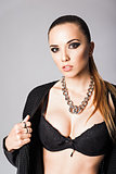 Fashion portrait of pretty young girl wearing black jacket, bra and necklace