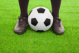 Soccer player's feet with ball  on an open playing field