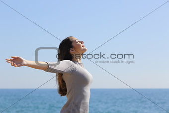 Happy woman breathing deep fresh air and raising arms on the beach