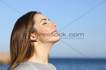 Woman portrait breathing deep fresh air on the beach