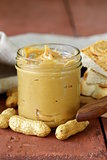homemade peanut butter with whole nuts on a wooden table