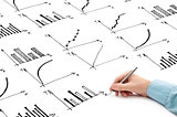 Businessman drawing bar chart and other info graphics in note pad