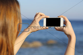 Back view of a woman taking photo with a smart phone camera
