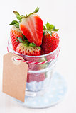 Fresh strawberries in glass with tag