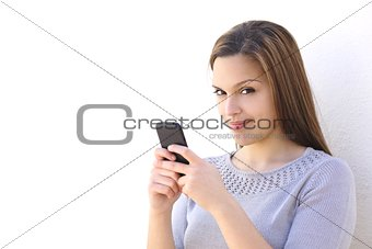 Beautiful woman texting on a smartphone and looking at camera