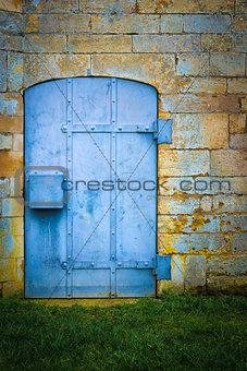 Old blue metal door set in stone