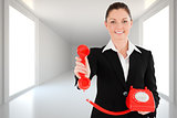 Composite image of charming woman in suit holding a red telephone