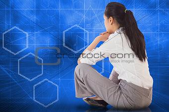 Composite image of businesswoman sitting cross legged