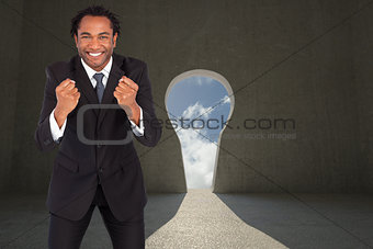 Composite image of successful businessman with raised arms