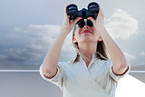 Composite image of businesswoman looking through binoculars