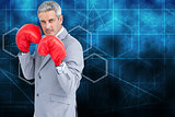 Composite image of tough businessman with boxing gloves