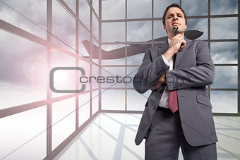 Composite image of thinking businessman holding his glasses