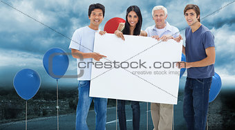 Composite image of smiling people holding and showing a big sign
