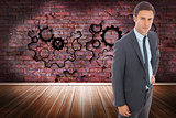Composite image of serious businessman standing with hand on hip