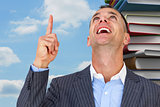 Composite image of cheerful businessman pointing upward
