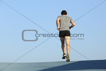 Back view of a jogger man running against blue sky