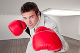 Composite image of confident businessman wearing boxing gloves
