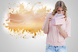 Composite image of curious young woman holding a gift while opening it