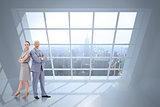 Composite image of serious businessman standing back to back with a woman