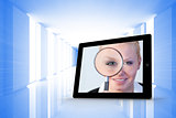Composite image of businesswoman holding magnfying glass on tablet screen