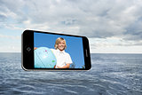 Composite image of blonde happy boy on smartphone screen