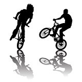 Silhouettes of bikers doing tricks