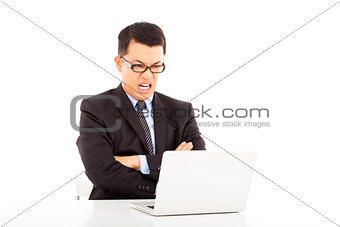 angry businessman look at laptop and cross arms