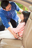 father help daughter to fasten a seat belt