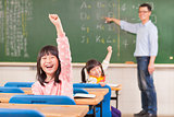 asian pupils raising hands during the lesson