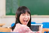 happy little schoolgirl holding digital tablet at desk