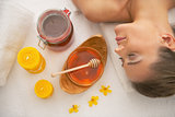 Young woman laying near honey spa therapy ingredients