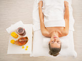 Young woman laying on massage table near honey spa therapy ingre