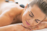 Portrait of young woman receiving hot stone massage