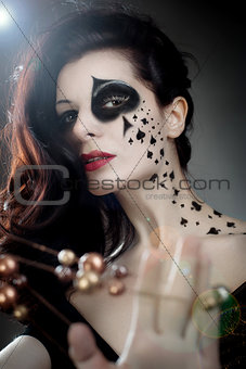 beautiful woman with make-up and body-art styled as playing card