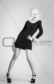 Beautiful girl in black dress with clutch in hand. Black and white