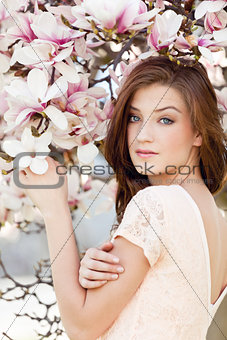 beautiful young woman and pink magnolia