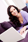 smiling woman on couch with notebook