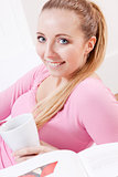 smiling young blond woman drinking coffee