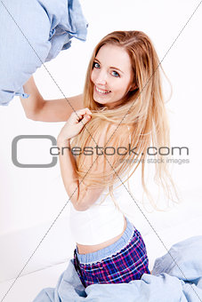attractive young woman pillow fight in bedroom