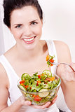 smiling woman eating fresh salad
