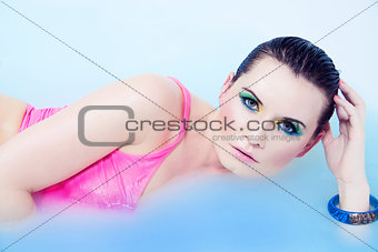 beautiful young woman with colorful makeup in water