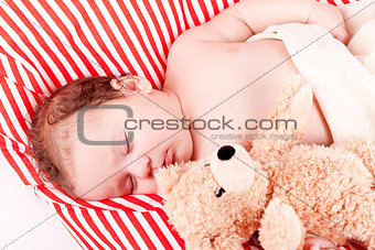 sleeping cute little baby on red and white stripes pillow