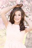 beautiful smiling woman and pink magnolia