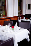 tables in restaurant with white tablecloth and elegant dish and silver wear
