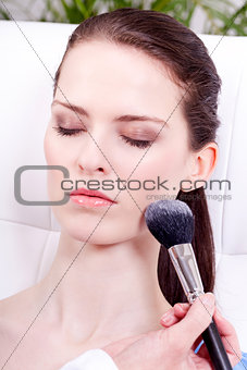 applying powder make up on face portrait