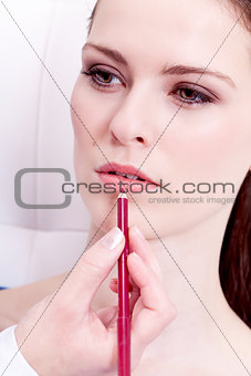 attractive woman doing make up lip liner