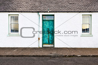 Green door and two windows on white wall house