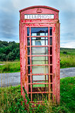 Detail of old red English phone booth in countryside
