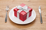 Valentine's day gift box on plate and silverware
