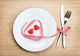 Valentine's Day heart shaped red ribbon over plate with silverwa